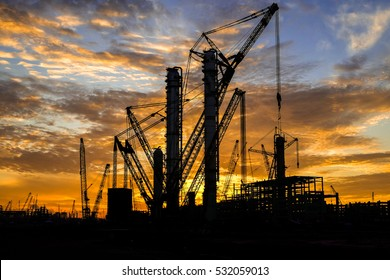 Silhouette shot of multiple cranes in construction sites with beautiful twilight sky.