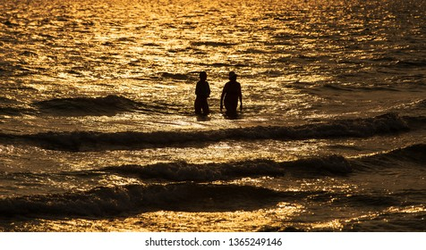 Silhouette shot of two people, couple walking in water at sea in twilight of senset.