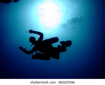 Silhouette of a sidemount diver