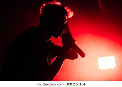 Silhouette of singer with microphone. Half face of singer. Red light.