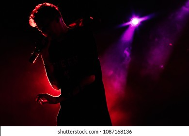 Silhouette of a singer with microphone on the stage in purple and red light. Beautiful illumination. Silhouette of singing man.
