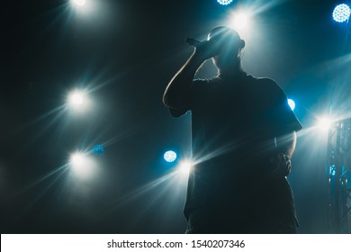 A silhouette of a singer on the stage. Good-looking background, bright stage lights.
