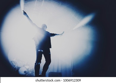silhouette of singer performing on stage at a concert in the fog. Dark background, smoke, concert  spotlights. vocalist raised his hand with a microphone