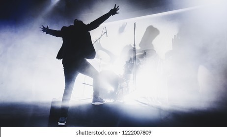 silhouette of singer performing on stage at a concert in the fog. Dark background, smoke, concert  spotlights. vocalist raised his hands