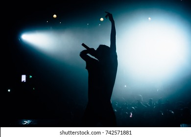 Silhouette of singer rising his hand opposite stage crowd. Floodlights lightning at the camera. Beautiful pool of white light on the background.