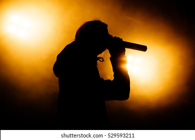 Silhouette of singer in yellow light