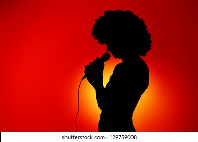 Silhouette of singing woman with microphone against red background
