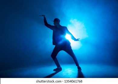 silhouette of single male break dancer isolated on blue neon background with light flare in middle