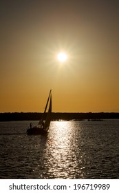 Silhouette of a single sailboat sailing off into a golden sunset.