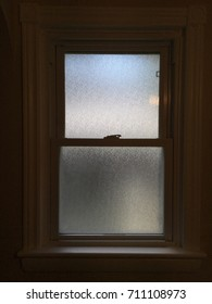 Silhouette of a single sand blasted window with light streaming through - warm tones suggest the break of damn.