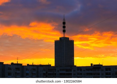 Silhouette of the single skyscraper building with aerial mast antenna on its roof against a colorful fire like sky and clouds with power lines going across the view