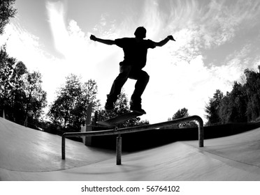 Silhouette of a skateboarder doing a trick