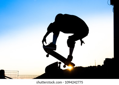 Silhouette of skateboarder during sunset