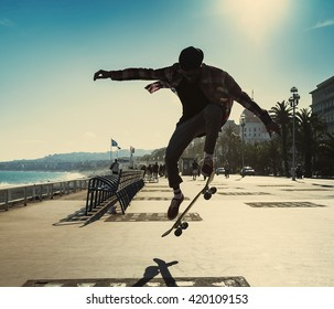 Silhouette of Skateboarder jumping in city on background of promenade and sea
