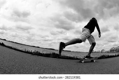 Silhouette of a skateboarder pushing around