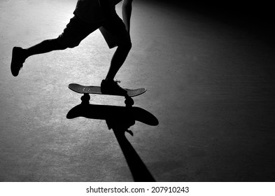 Silhouette of a skateboarder pushing through the skate park.