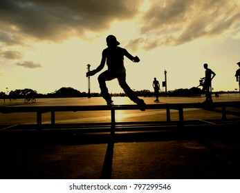 Silhouette of skater performing maneuvers with sun in background