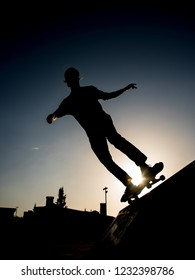 Silhouette of a Skater riding the skate in a half pipe in a skate park in lisbon