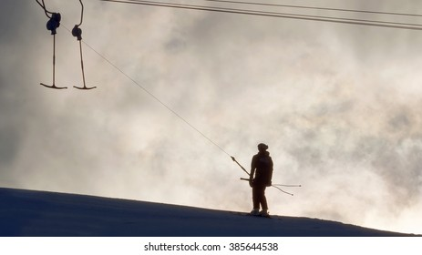 Silhouette of a ski lift and and lonely skier in evening light