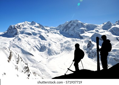 Silhouette of skiers high in mountains ready for freeride. Snowy hills and sun in front of them. Couple of freeriders on the hill.