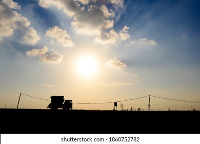 Silhouette of skip truck in the oilfield at sun set