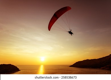 Silhouette of sky diver flies on background of sunset sky and sea. Phuket island, Thailand