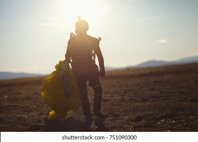 Silhouette skydiver with a parachute in the hands of a person walking on the field after landing. Parachutist after the jump, silhouette close-up.
