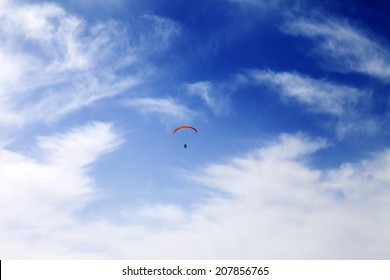 Silhouette of skydiver at windy sky