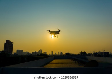 Silhouette skyline with quadcopter flying on the city building sunset