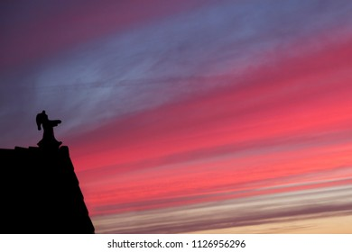 Silhouette of sleepwalking figure on the roof at sunset.