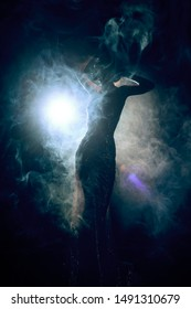 Silhouette of a slim, artistic girl wearing an elegant evening dress in theatrical fog. Sensual, conceptual and fashionable design. Copy space.