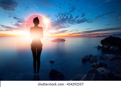 Silhouette of a slim girl standing on a beach watching solar eclipse