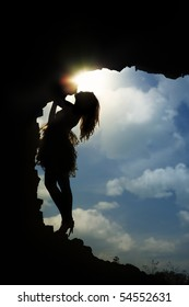 Silhouette of the slim lady standing in the dark cave against the cloudy sky and sun