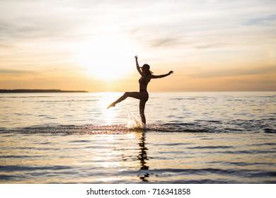silhouette of slim sexy girl in bikini walking on the beach at sunset