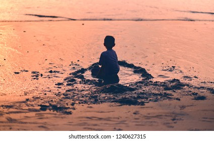 Silhouette of small  boy, kid, sitting alone on the beach at sunset time. kid sitting isolated on a beach view from behind, concept of solitude and alone.