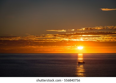 Silhouette of a small fishing boat crossing a sunrise beam on the Sea of Cortez.