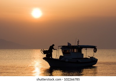 Silhouette of a small fishing boat at sunrise on a calm mediterranean sea