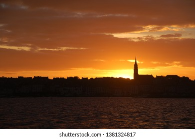 Silhouette of a small town during sunset, sundown seen from the sea