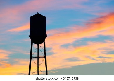 A silhouette of a small town water tower against a brilliant early morning sky.