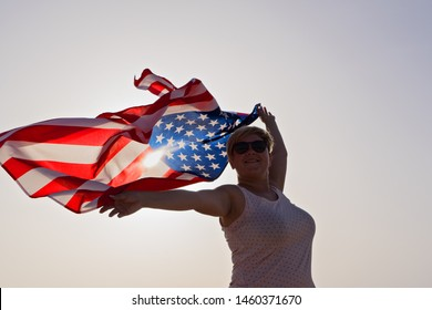 Silhouette of smiling woman in sunglasses with raised hands and waving flag of United States of America against sunset sky