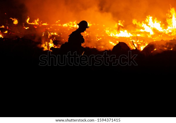 Silhouette of a smoke jumper fireman walking the parameter of a wildfire