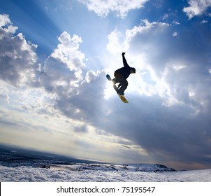 Silhouette the snowboarder jumping high in the blue sky and clouds