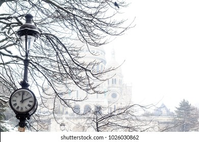 Silhouette of the snowy Sacre-Coeur cathedral visible through naked winter tree branches. Lamppost with a clock is on the foreground of the picture.