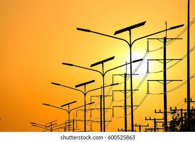 silhouette of Solar energy light pole road with sunset