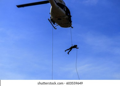 silhouette Soldier Jump rope from helicopter in blue sky