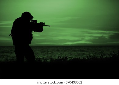 Silhouette of soldier with rifle on a sunset dark background. War, military and danger concept.