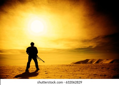 Silhouette of soldier with sniper rifle standing under scorching sun in the mountains