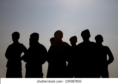 Silhouette of soldiers line up against the sun.