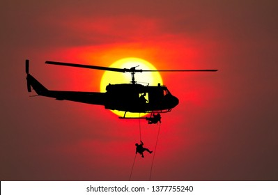 Silhouette Soldiers rappel down to attack from helicopter with warrior beware danger On the ground sunset Background blur and copy space add text ( Concept stop hostilities To peace)