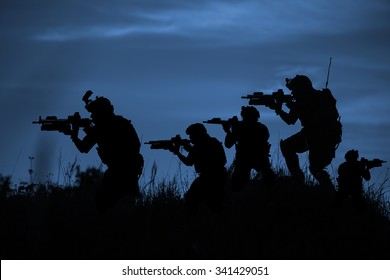 Silhouette of soldiers with rifle on a dark blue background